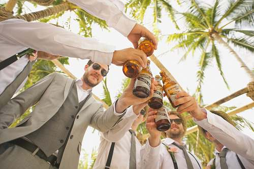 person low angle of men holding beer bottles and having a toast wedding