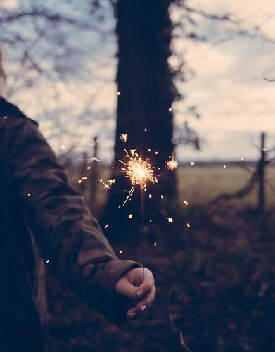 human person holding sparkler at daytime person
