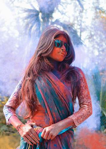 human selective focus photo of woman wearing green and brown shawl covered with powder person