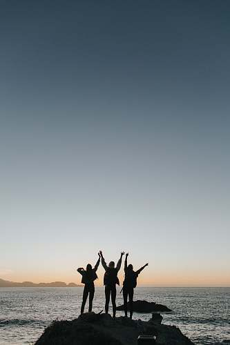 grey silhouette photography of persons raising hands while standing on island sea