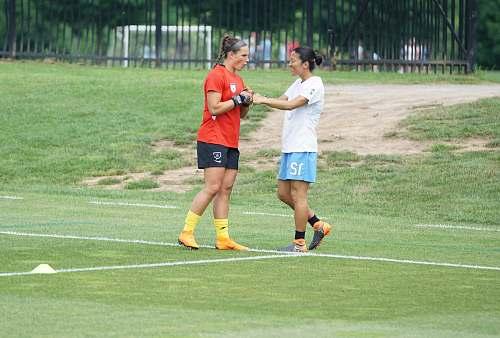 human two women fist bumping on field sport
