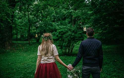 human woman and man standing holding hands facing trees back