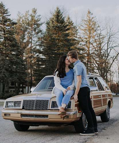 human man kissing woman while sitting on brown car people