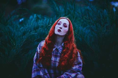 human photography of red-haired woman standing near leafed plants people