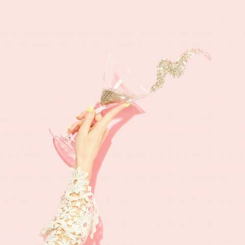 party person holding clear martini glass glitter