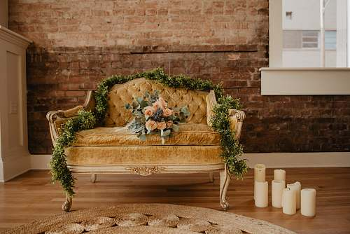 furniture vacant tufted beige loveseat with bouquet of orange rose flowers couch