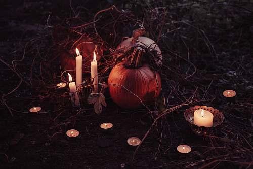squash pumpkin between lighted candles halloween