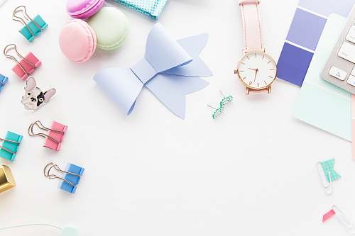 pastel round white and gold-colored analog watch beside paper ribbon styled stock