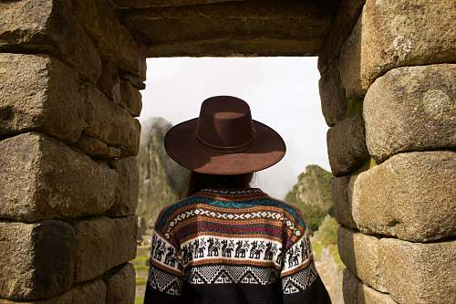 clothing woman standing under brown rock formation hat