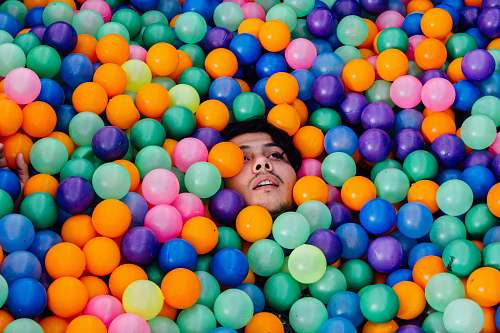 man man lying in ball pit balloon