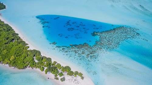 blue aerial photo of island during daytime coast