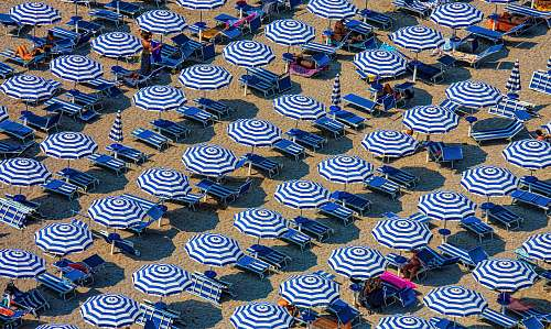 summer aerial photography of blue-and-white patio umbrellas sand