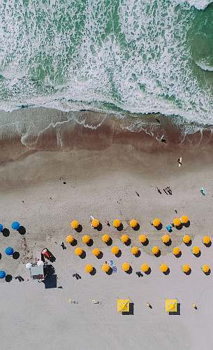 outdoors aerial photography of umbrellas on beach snow