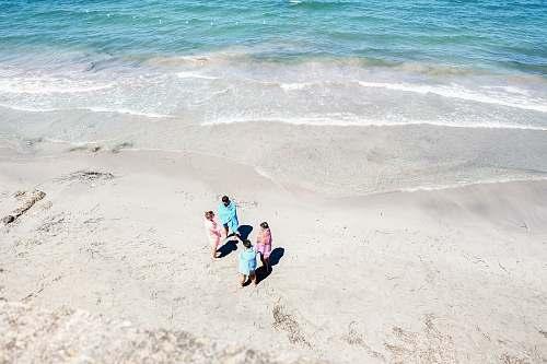 water four people standing on seashore coast