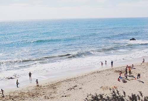 water group of people standing on seashore sea
