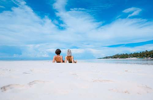 summer two women lying on white sand facing beach under blue sky water