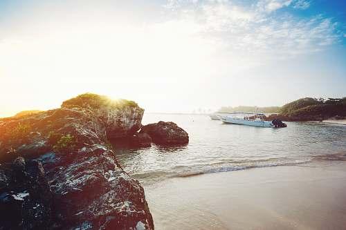 water white boat near seashore during daytime sea
