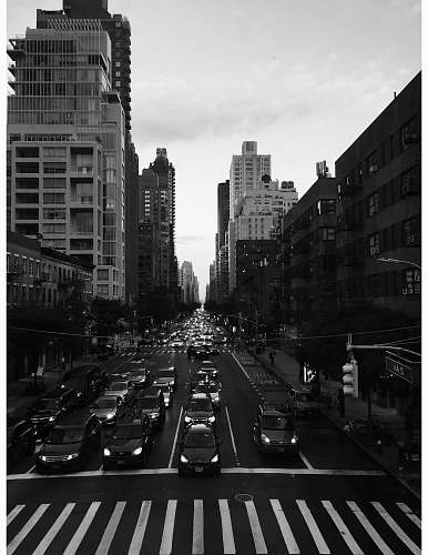 city grayscale photography of people walking on pathway near buildings and different vehicles on road road