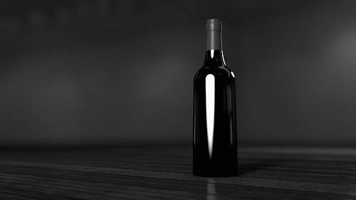black-and-white black glass bottle on brown surface wine