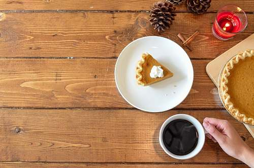 thanksgiving slice of pie with whipped cream on ceramic plate near coffee bowl