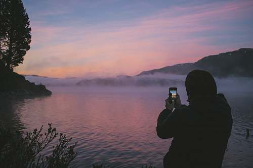 person person taking photo of foggy river people