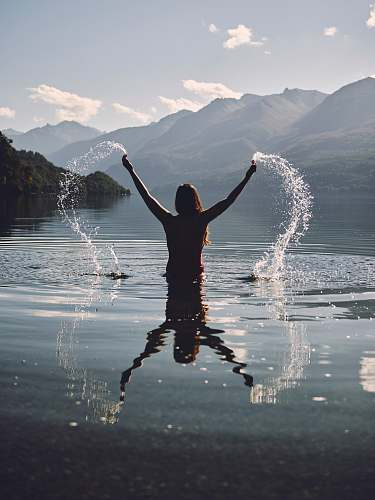 person woman raising her two hands with splashing water people