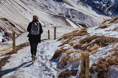 person woman walking near mountain covered by snow during daytime people