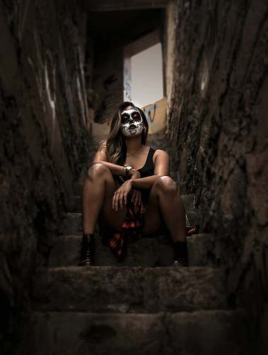 people woman wearing skull face paint sitting on stairs person
