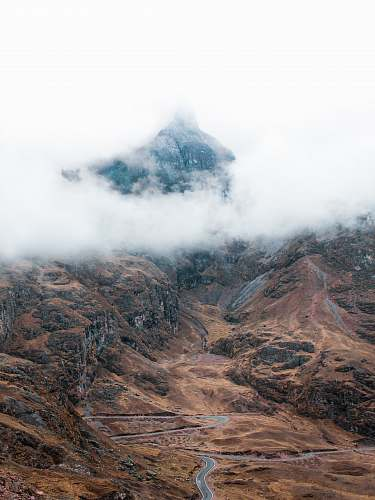 peru aerial photo of gray road near mountain under white clouds during daytime cusco