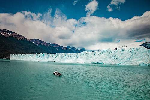 ice aerial photography of white boat on body of water beside ice block cliff during daytime mountain