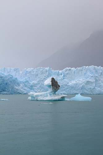 ice iceberg on body of water at daytime glacier