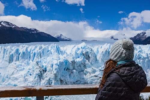 mountain person wearing black hooded jacket seeing snow mountain during daytime snow
