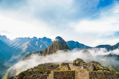 outdoors photo of ruins beside wall covering fogs peru