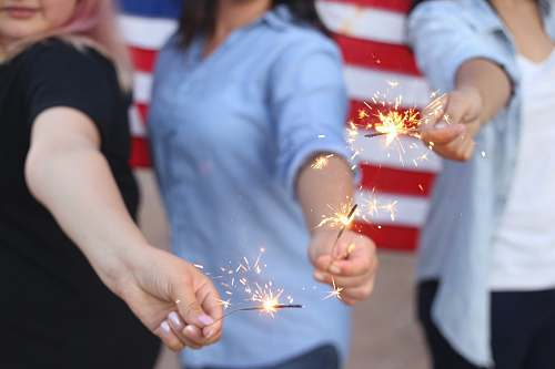 human three person holding sparklers person