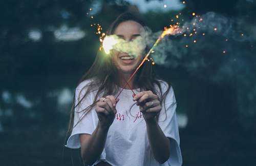 human woman holding two sparklers person