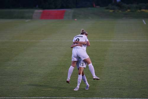 person woman hugging her co player on green field human