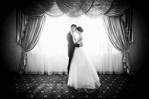 black-and-white grayscale photography of couple facing in front curtain wedding