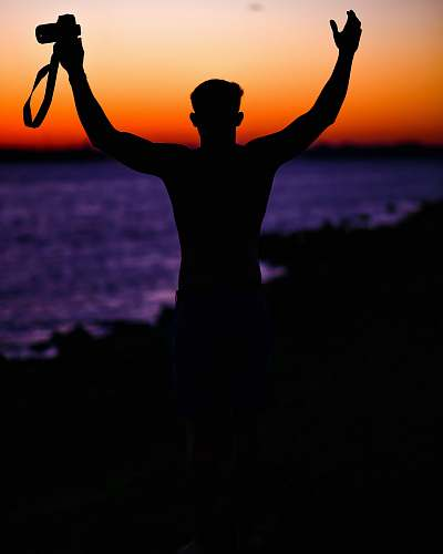 sunset person holding DSLR camera silhouette
