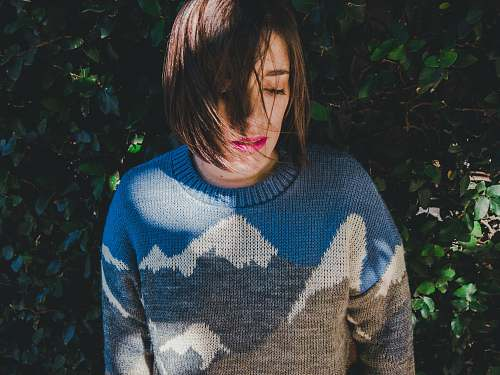 human woman wearing sweater near green grass wall people
