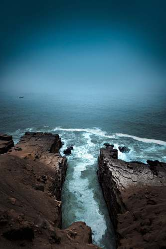 ocean aerial photography of cliff near body of water during daytime sea