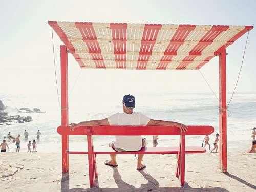 people man sitting on bench near beach silveira