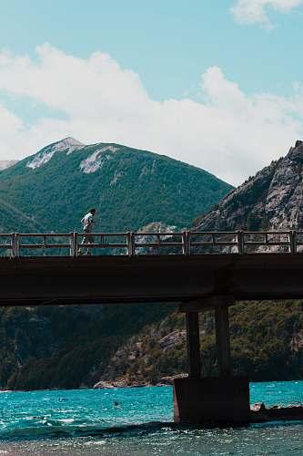 freeway man running on concrete walk bridge above body of water during daytime person