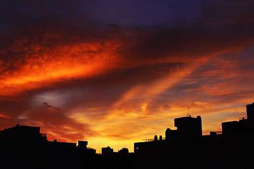 sunset silhouette of buildings under scarlet sky sunrise