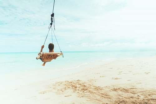 toy man swing beside body of water water
