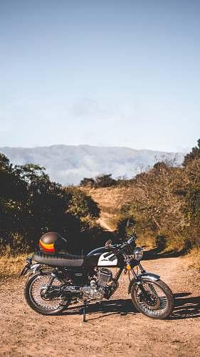 vehicle black and orange helmet on black and white standard motorcycle motorcycle