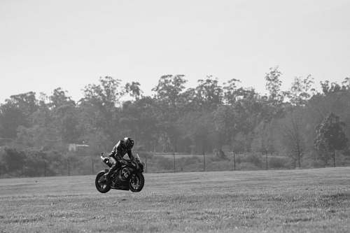 vehicle grayscale photo of man riding sports bike black-and-white