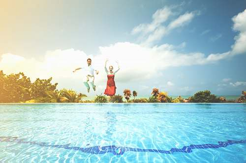 pool man and woman jumping onto pool sky