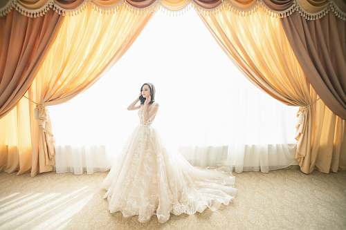 bride photo of woman wearing white gown near window curtain home decor