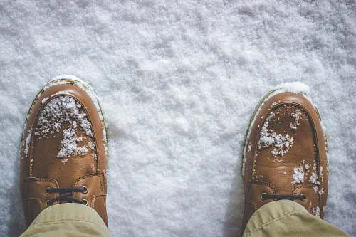 shoe top view photography of person standing on snow covered field feet