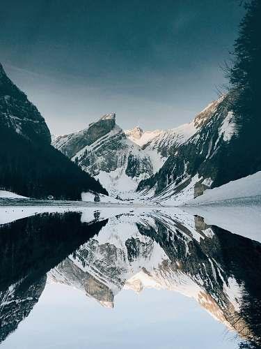 snow snow-covered mountain near lake under blue sky mountain